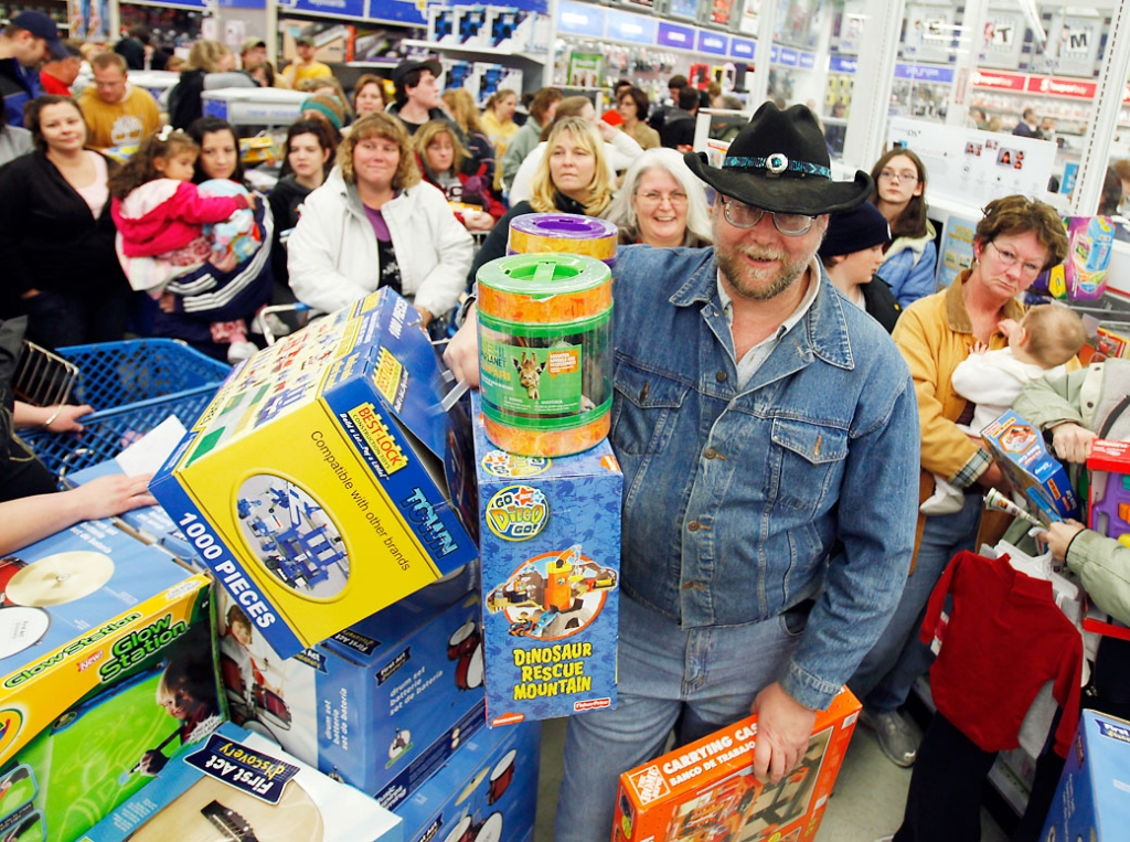 "Black Friday holiday Greg Inman of Shermans Dale, Pa., waits in a checkout line with other shoppers at Toys ""R"" Us in Camp Hill, Pa., early Friday morning, Nov. 27, 2009. (AP Photo/Carolyn Kaster)"